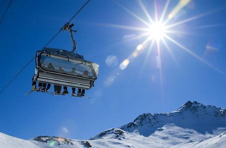 skiers in a chairlift backlit by the sun and spreading sunflares