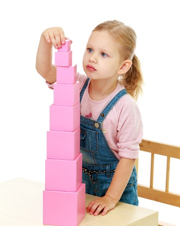 Foto de Little girl collects the pink pyramid.Childhood education development in the Montessori school concept. Isolated on white background. - Imagen libre de derechos