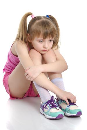 Photo pour Girl gymnast sits on the floor and cries - image libre de droit