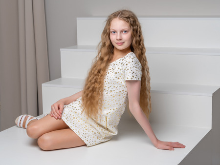 Photo pour Beautiful little girl is sitting on the white staircase. - image libre de droit