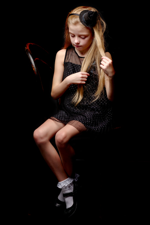 Photo pour Little girl straightens her hair in the studio on a black backgr - image libre de droit