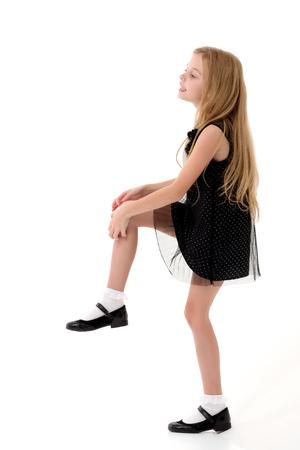 Foto de The little girl is standing on one leg. - Imagen libre de derechos