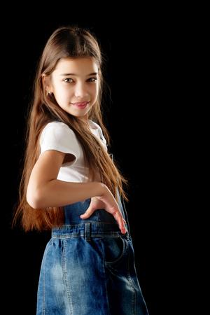 Foto de Little girl in denim clothes on a black background. - Imagen libre de derechos
