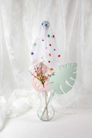 Photo pour Lace curtain ghost made with a disco ball covered with multicolored flowers on the sheet with a bouquet of flowers in a vase in front of it. Offbeat and pop atmosphere. minimal color still life photography - image libre de droit