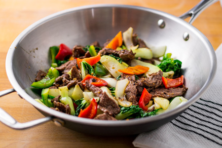 Flank steak beef, peppers, onions and bok choy stir fried in an asian wok. It's easy to eat healthy vegetables in a delicious stir fry!