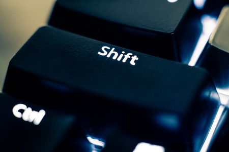 Foto de Macro photo of the shift key on a mechanical switch keyboard. The letters are etched on black plastic ABS keycaps to reveal the white led backlight. Other keys are out of focus in the background. - Imagen libre de derechos