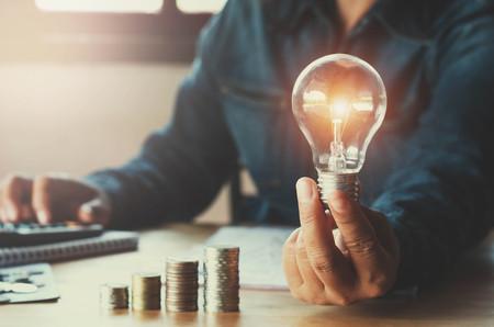 Foto de business accountin with saving money with hand holding lightbulb concept financial background - Imagen libre de derechos