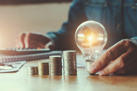 Photo pour business accountin with saving money with hand holding lightbulb concept financial background - image libre de droit