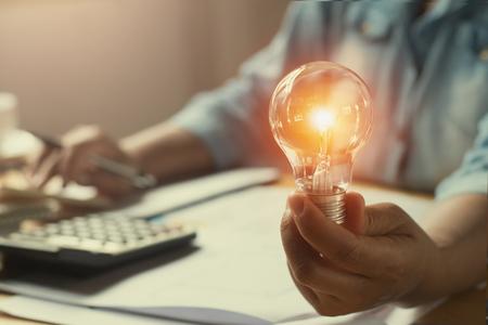 Photo pour hand woman accountant holding light bulb, new idea with innovation concept - image libre de droit