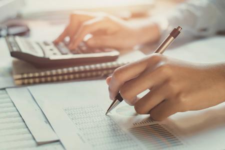 Foto de accountant working on desk to using calculator with pen - Imagen libre de derechos