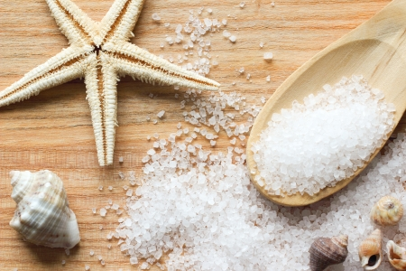 Photo pour Sea salt crystals in wooden spoon with sea shells and starfish on wooden background - image libre de droit