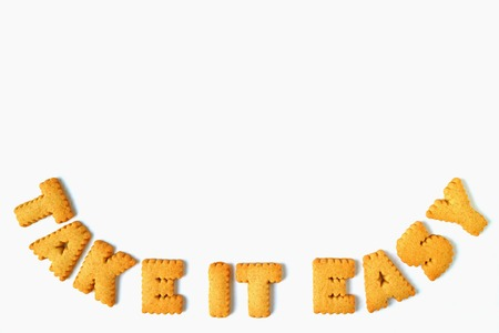 Photo pour The word TAKE IT EASY made with alphabet shaped biscuits, isolated on white background with free space for text and design - image libre de droit