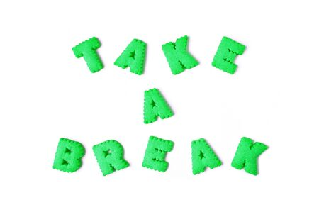 Photo pour The word TAKE IT EASY spelled with lime green color alphabet shaped biscuits on white background - image libre de droit