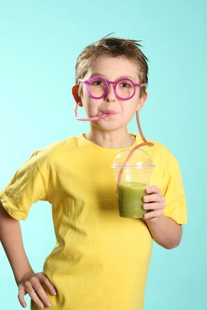 A boy sips a healthy juice containing wheat and barley grass through a crazy straw.Wheatgrass in juice has been proven over many years to benefit people in numerous ways: cleansing the lymph system, building blood, removing toxic metals from the cells, n