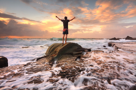 Foto de Teen boy stands on a rock among turbulent ocean seas and fast flowing water at sunrise   Worship, praise, zest, adenture, solitude, finding peace among lifes turbulent times   Overcoming adversity   Motion in water - Imagen libre de derechos