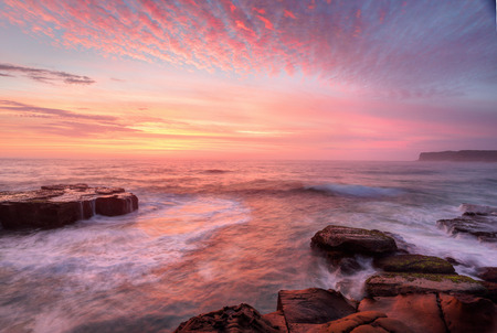 Photo pour Summer sunrise skies  light up with colour throwing warmth across the  landscape and whitewater seas wash around the rocks at North Avoca Central Coast NSW Australia - image libre de droit
