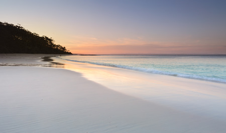 Photo pour Serenity and peace at sundown on Murrays Beach in Booderee National Park, Jervis Bay Australia.  Pretty soft colours in the sky and reflecting in the wet sand.  A tranquil place to unwind from life's busyness or troubles - image libre de droit