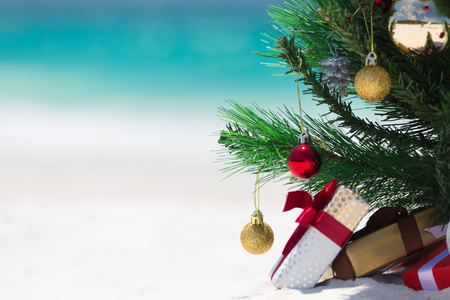 Photo pour Christmas time spent at the beach in summer. A christmas tree surrounded by presents on a beautiful sandy beach.  Shallow dof with space for copy - image libre de droit