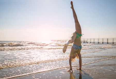 Photo for young woman is making the wheel on the beach - Royalty Free Image
