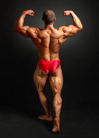 Photo pour Young bodybuilder man flexing back double bicpes pose, showing his huge trapezius, rhomboid, levator, latissimus dorsi and legs muscles. Studio shot on black background. - image libre de droit