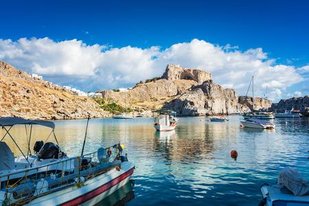 Foto de Fishing boats and sail boat in St. Paul´s bay, Lindos acropolis in background (Rhodes, Greece) - Imagen libre de derechos
