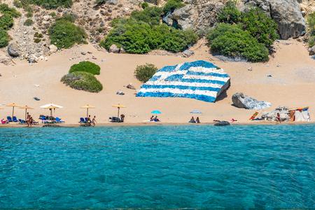 Foto de Tsambika beach with golden sand with big Greek flag painted on rock (RHODES, GREECE) - Imagen libre de derechos