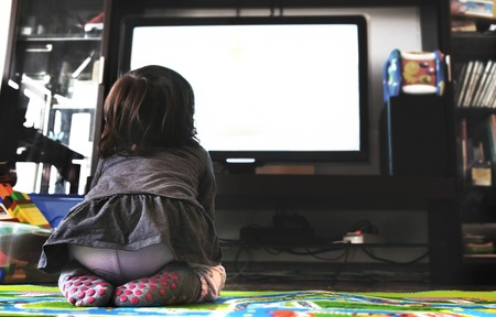 Foto de newborn baby watch tv on the carpet in livingroom socks back view - Imagen libre de derechos