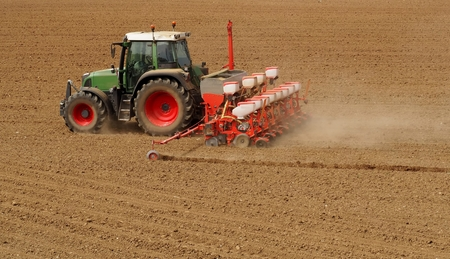 Photo pour Tractor with a modern field in springtime. Side back view - image libre de droit
