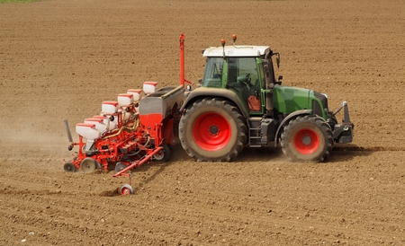 Photo pour Tractor with a modern field in springtime. Side view. Plowed land on background - image libre de droit