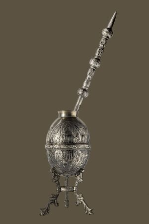 Photo for Ancient Argentine mate in silver worked in relief with straw on a brown background - Royalty Free Image