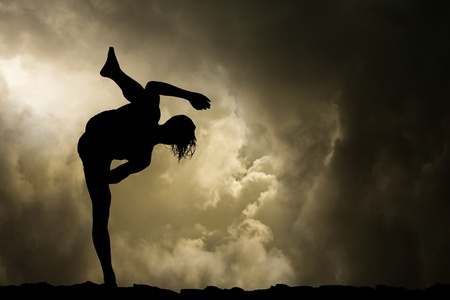 Man Practises Martial Arts High Kick Silhouette on Stormy Sky Background