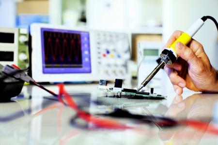 Foto de soldering electronic parts on a printed circuit board - Imagen libre de derechos