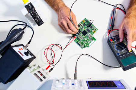 Foto de Development of electronic devices in the modern electronics laboratory, on a table,  microprocessor oscilloscope and  multimeter - Imagen libre de derechos