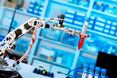 Foto de robot manipulates chemical tubes in the laboratory - Imagen libre de derechos