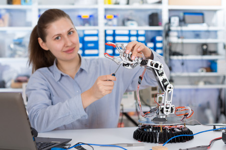 Foto de schoolgirl adjusts the robot arm model, girl in a robotics laboratory - Imagen libre de derechos