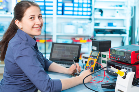 Photo pour Woman with a tester and a printed circuit board - image libre de droit