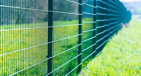 Photo pour Metal fence in green field - image libre de droit