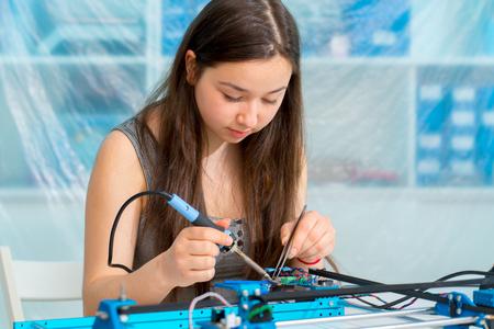 Foto de Student girl in electronics laboratory, experiment with microcontroller and robot cnc module - Imagen libre de derechos