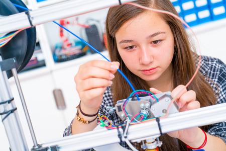 Foto de Schoolgirl prints 3d model from plastic on 3d printer - Imagen libre de derechos