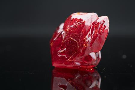 Foto de Red natural crystal mineral on a black background - Imagen libre de derechos