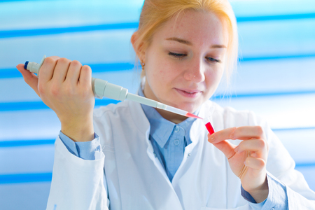 Foto de Laboratory assistant in the medical laboratory control a microbiological analysis of the blood. Using a pipette and a test tube in the laboratory - Imagen libre de derechos