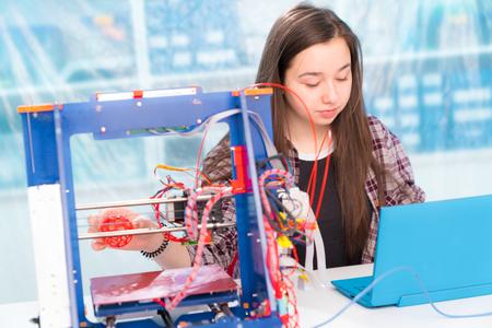 Foto de Girl schoolgirl with a 3D printer - Imagen libre de derechos