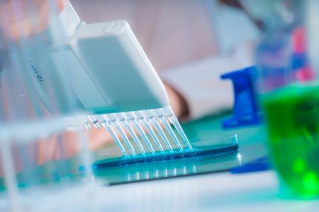 Foto de Microbiological laboratory scientist woman with multi channel pipette going DNA test - Imagen libre de derechos