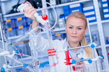 Foto de Female laboratory assistant with chemical experiment in scientific laboratory. Female medical or scientific researcher using test tube on laboratory. - Imagen libre de derechos