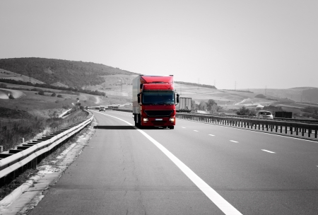 Photo for Red truck on highway is moving rapidly - Royalty Free Image