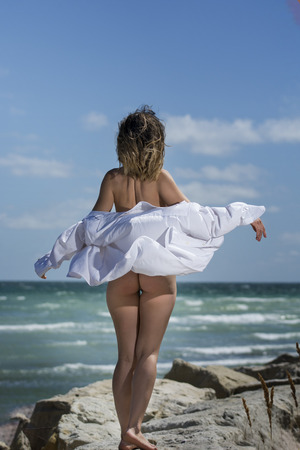 Photo for Beautiful young sexy nude woman enjoying nature by the sea - Royalty Free Image
