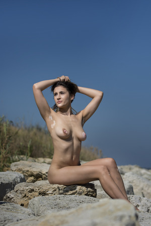 Photo for Beautiful young sexy nude woman enjoying nature by the sea. - Royalty Free Image