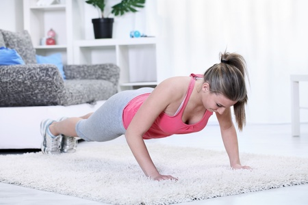 Young woman looking down while doing push-ups in living room