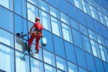 Foto de window cleaner working on a glass facade modern skyscraper - Imagen libre de derechos