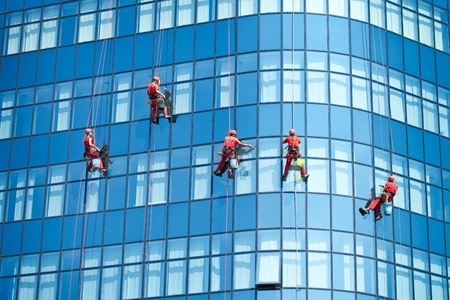Photo pour Five workers washing windows in the office building - image libre de droit